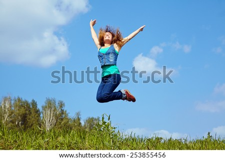 pretty young woman jumping on the sky background. happy girl outdoor