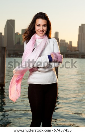 Pretty young woman lifestyle with winter clothing along a seawall on the bay with a downtown skyline at sunset. - stock photo