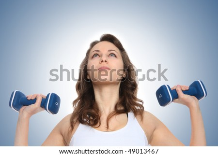 Pretty young woman lifting weights as a fitness exercise