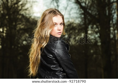 Pretty young woman long blond hair in winter forest wearing black leather jacket and blue shirt - stock photo