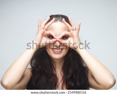 Pretty young woman looking for something with wide open eyes and imaginary binocular. - stock photo