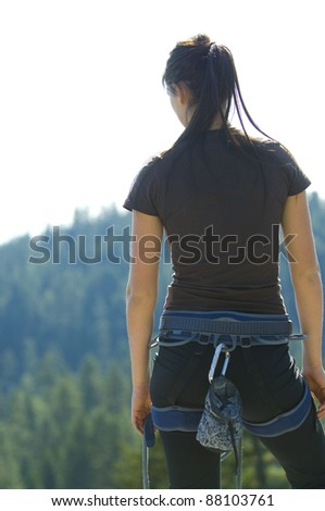 Pretty Young Woman looking off a cliff into valley - stock photo