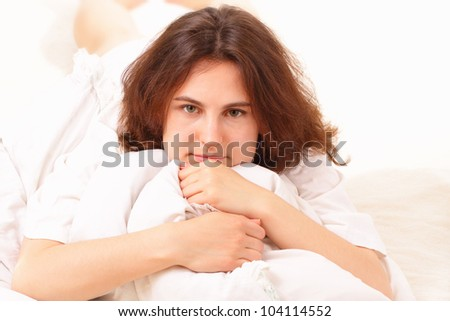 Pretty young woman lying in bed - stock photo