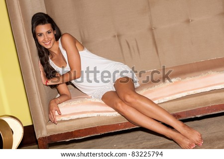 Pretty young woman lying on a art deco sofa in a trendy South Beach hotel lobby in Miami. - stock photo