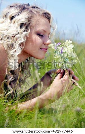 Pretty young woman lying on grass and smelling flowers