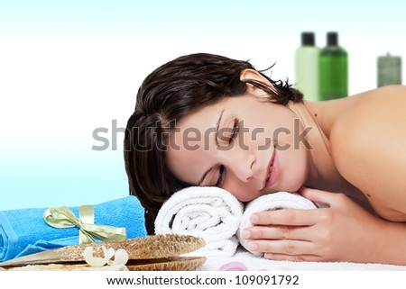 Pretty young woman lying on towels, surrounded by cosmetics/Beauty Therapy - stock photo