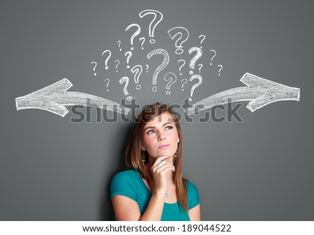 Pretty young woman making a decision with arrows and question mark above her head - stock photo