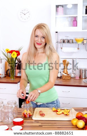 Pretty young woman making canned fruits in the kitchen