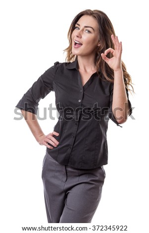 Pretty young woman making Ok sign with her left hand, whilst her right hand is on her hip.  Isolated on white background. - stock photo