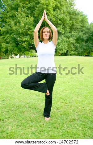 pretty young woman meditate outdoor in a park. concept for yoga or wellbeing - stock photo