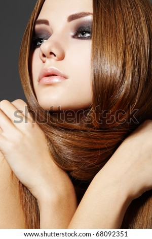 Pretty young woman model with shiny smooth hairstyle and brown smoky make-up. Health, beauty, wellness, hair and make-up. Beautiful fashion hairstyle - stock photo