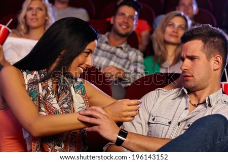 Pretty young woman molesting young man at movie theater. - stock photo