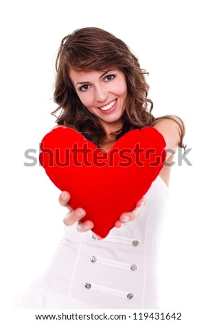 Pretty young woman offering a red heart to us - stock photo