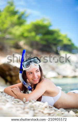 Pretty, young woman on a beach during her summer vacation with snorkel lying on beach with snorkeling mask and fins smiling happy enjoying the sun on a sunny summer day. - stock photo