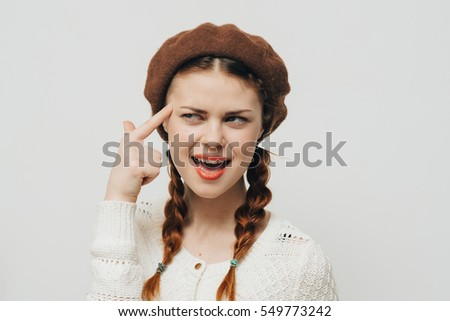 Pretty young woman on a light background hamming for the camera
