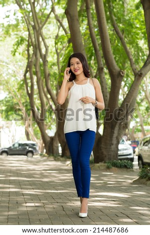 Pretty young woman on cellphone walking outdoors - stock photo