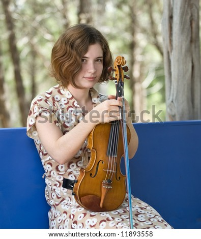 Pretty young woman or teenager holding violin and bow, seated on blue bench outdoors