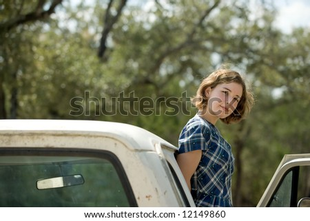 Pretty young woman or teenager standing on running board of vintage  truck looking at viewer, blurred foliage in background