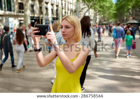 Pretty young woman photographing urban view with mobile phone camera during summer journey, gorgeous female tourist taking picture with her smart phone while standing outdoors in urban setting street - stock photo