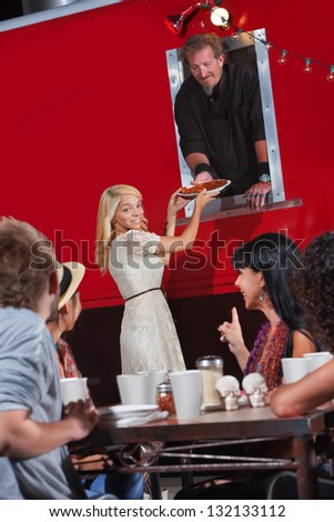 Pretty young woman picking up pizza order at food truck - stock photo
