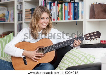 Pretty young woman plays guitar on the couch at home - stock photo
