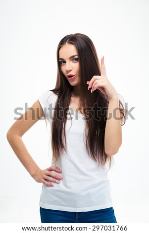 Pretty young woman pointing finger up isolated on a white background. Looking at camera - stock photo