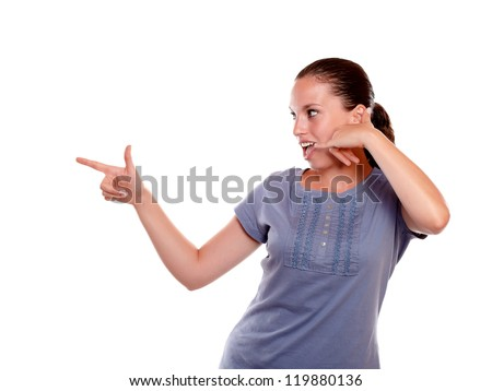 Pretty young woman pointing right saying call now on blue shirt against white background - stock photo