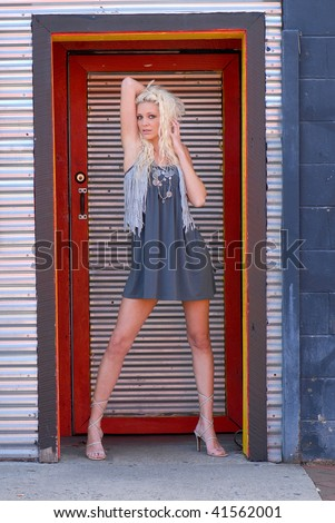 Pretty Young Woman Posing in colorful Doorway - stock photo