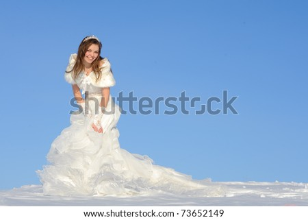 pretty young woman posing in wedding dress with train, on winter snow