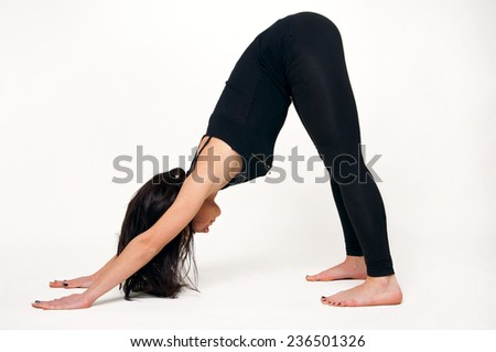 Pretty young woman practicing yoga, doing downward-facing dog pose. Over white background, copy space - stock photo