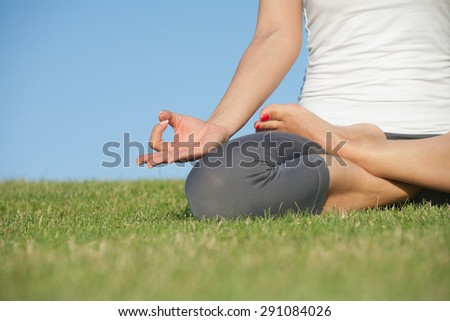 Pretty young woman practicing yoga on the grass. Yoga girl in white singlet sitting in lotus pose. - stock photo