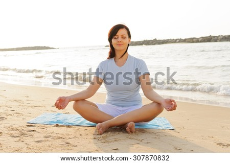 Pretty young woman practising yoga on the beach