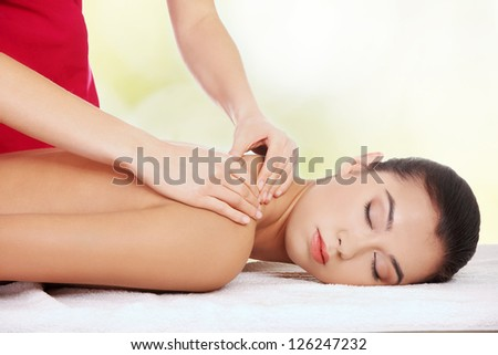 Pretty young woman relaxing being massaged in spa saloon - stock photo