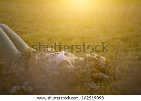 Pretty young woman relaxing in sunset