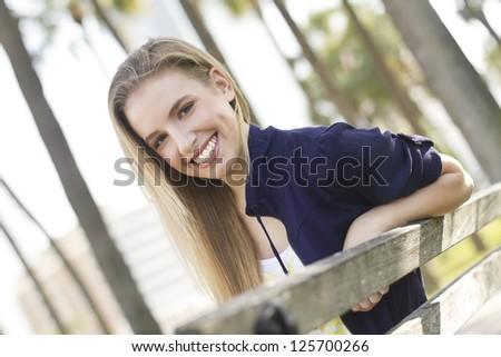 Pretty young woman relaxing on a bench - stock photo