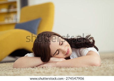 Pretty young woman relaxing on the carpet lying on her stomach with her head on her folded arms with her eyes closed and a smile of pleasure - stock photo