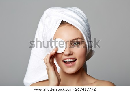 Pretty young woman removing make up, on gray background