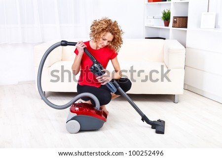 Pretty young woman repairing vacuum cleaner at home - stock photo