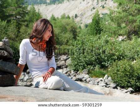 Pretty young woman resting on a large boulder along the hiking trail in the Morteratsch Glacier Valley in the Bernina Mountain Range of the Bundner Alps in Switzerland.