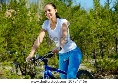 Pretty young woman riding a bicycle - stock photo