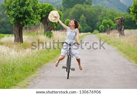 Pretty young woman riding bike in a country road. - stock photo