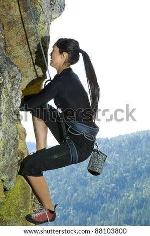 Pretty Young Woman Rock Climbing a cliff with ropes - stock photo