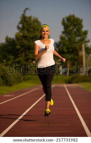 Pretty young woman running on a track on a summer afternoon