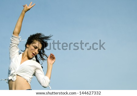 Pretty young woman showing gesture that everything is Victory, against blue sky. - stock photo