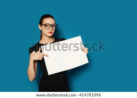 Pretty young woman showing on empty blank board. Colorful studio portrait isolated on blue background. Space for text.  - stock photo
