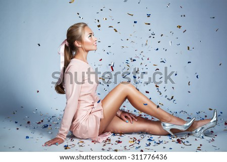 Pretty young woman sitting and smiling under confetti. Fashion portrait.  - stock photo