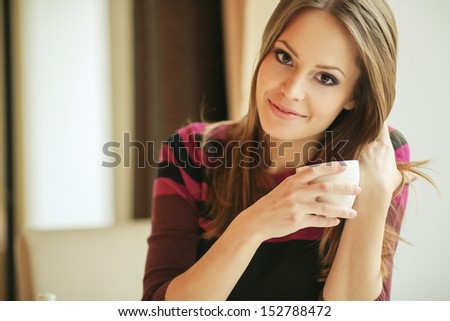 pretty young woman sitting in a cafe with a cup of tea - stock photo