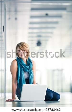 Pretty, young woman sitting in a modern corridor, working on her laptop computer (shallow DOF; color toned image) - stock photo