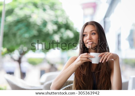 pretty young woman sitting in the cafe with a cup of tea or coffee. Charming woman in a restaurant.  - stock photo