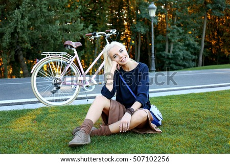 Pretty young woman sitting on green lawn near bicycle